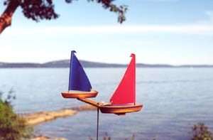 Two model sailboats that spin in the wind, a fun garden whirlygig.